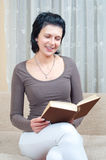 Pretty elegant woman reads book on the couch Royalty Free Stock Image