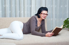 Pretty elegant woman reads book on the couch Stock Photography