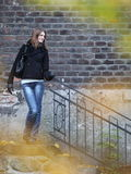 Pretty & elegant young woman outdoors. Pretty & elegant young woman standing by a small staircase outdoors in a park on a lovely fall day Stock Photography