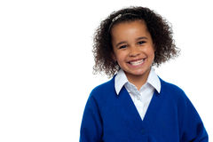 Pretty elementary school girl, curly hair. Happy elementary school girl flashing a smile isolated over white Stock Images