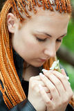 Pretty emotional girl with african braids. Holds a blossoming cherry twig Stock Photos