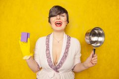 Beautiful bright brunette in a Bathrobe holds a pan and a sponge for washing dishes. young woman housewife on yellow studio backgr stock images