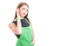 Pretty employee with apron listening curious something. On white background with copy space stock image