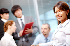 Pretty employer. Portrait of smart employer looking at camera on background of people working stock image