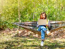 Pretty engineer woman use her laptop on hammock to online connection with workmate also with the concept of business working also stock photo