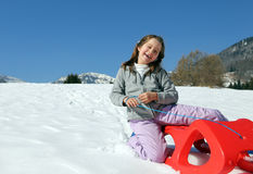 Pretty enjoyed girl plays with red sled in the mountains Stock Photography