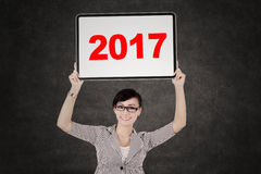 Pretty entrepreneur holding billboard with 2017 Stock Photography
