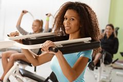 Pretty ethnic girl exercising on weight machine. At the gym, smiling Stock Photo