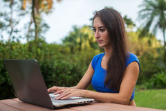 Pretty European female student using her laptop studying outdoors. Girl socializing on  pc in the garden. Royalty Free Stock Image