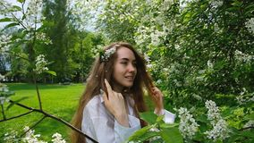 Pretty European girl model posing on camera in blossoming bird cherry. A woman with long fluffy hair and a branch on her stock video footage