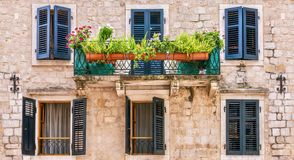 Pretty European house facade, with window shutters, balcony, and potted plants. stock photos