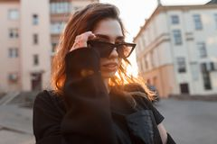 Pretty european stylish young woman hipster in dark sunglasses in a stylish t-shirt with sexy lips poses near vintage buildings stock images