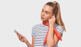 Young woman with ponytail, wearing striped t-shirt, stylish red scarf on neck, relaxing with closed eyes listening to songs. Pretty European young woman with stock photos