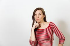 Pretty European happy brown-haired woman with healthy clean skin dressed in casual longsleeve on a white background. The pretty European young worried and Royalty Free Stock Images