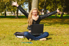 Pretty excited girl with a laptop. In the park Stock Image