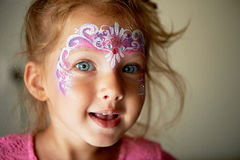 Pretty exciting blue-eyed girl of 2 years with a face painting. Pretty exciting blue-eyed girl of 2 years with a pink face painting royalty free stock photography