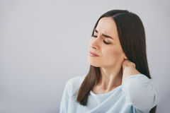 Pretty exhausted woman closing eyes and standing against white wall. royalty free stock photography