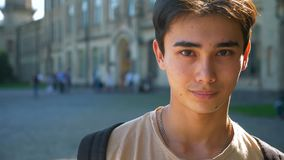 Pretty face of asian man looking at camera in slow motion with urban view behind stock video footage