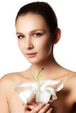 Pretty face of beautiful young woman with lily on hands - white Royalty Free Stock Image