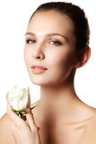 Pretty face of beautiful young woman with rose on hands - white Stock Photography