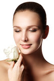 Pretty face of beautiful young woman with rose on hands - white Stock Images