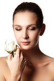 Pretty face of beautiful young woman with rose on hands - white Royalty Free Stock Photo