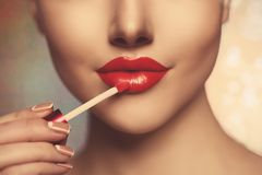Pretty face beauty lady Red woman lips close up. Beautiful model. Girl with lipstick. Products Treatment. She gets gloss Stock Photos