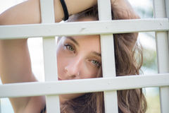 Pretty face of a lady looking the camera behind of a wooden lattice Royalty Free Stock Photo