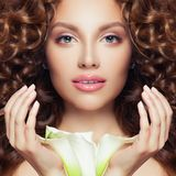 Pretty face. Perfect model woman with curly hair, clear skin and flower royalty free stock photography