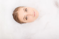 Pretty face in white fluffy foam Royalty Free Stock Photography