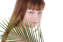 Pretty face of woman hiding behind leaf Stock Images