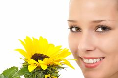 Pretty face with a yellow sunflower. Smiling pretty face with bright eyes and a sunflower Royalty Free Stock Photo