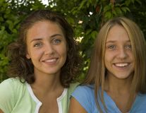 Pretty faces smiling. Two pretty teenage girls smiling royalty free stock image