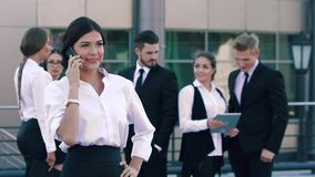 Pretty fair-skinned business woman having a phone call and her coworkers talking in the background stock footage