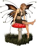 Pretty Fairy Sitting on a Toadstool Royalty Free Stock Photo