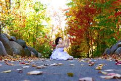 Pretty fall colors. A child sitting on a path in the fall wearing a purple dress Stock Photography