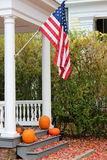 Pretty fall scene at home with flag and pumpkins Stock Images