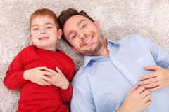 Pretty family is relaxing on floor together. Cute young father and his son are lying on flooring near each other. They are looking forward and smiling Stock Images