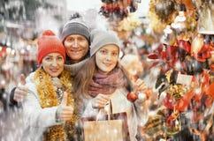 Pretty family of three choosing Christmas star flower Royalty Free Stock Photos