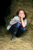 Pretty farm girl. A smiling pretty young farm girl with long blond hair, in the barn by the hay with mud boots on Stock Image