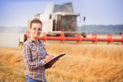 Pretty farmer girl with folder in wheat fild. Pretty farmer girl in glasses with hair tied in a ponytail keeps a harvest accounting in the folder. Sunny day Stock Images
