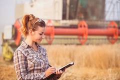 Pretty farmer girl with folder in wheat fild. Pretty farmer girl in glasses with hair tied in a ponytail keeps a harvest accounting in the folder. Sunny day Royalty Free Stock Images