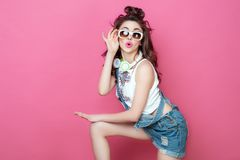 Pretty fashion cool smiling girl with headphones knitted bag sunglasses wearing a colorful clothes with curly hair dancing happy o. Pretty fashion cool smiling Royalty Free Stock Photos