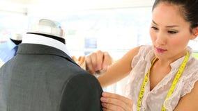 Pretty fashion designer adjusting suit stock video