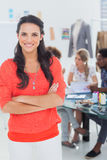 Pretty fashion designer with arms crossed in bright office. Smiling at camera royalty free stock photo