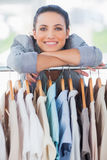 Pretty fashion designer leaning on clothes Royalty Free Stock Image