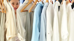 Pretty fashion designer looking through her clothing rail stock footage