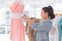 Pretty fashion designer measuring dress on a mannequin Stock Image