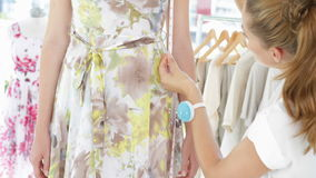 Pretty fashion designer measuring floral dress on a model Royalty Free Stock Photography