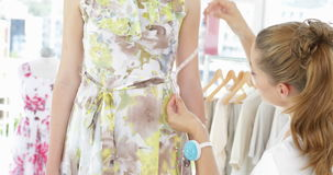 Pretty fashion designer measuring floral dress on a model stock footage